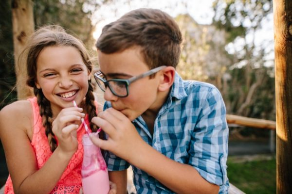 happy young boy and girl drinking smoothie together
